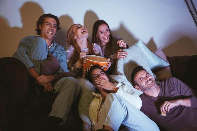 Groep gelukkige vrienden die op een film letten