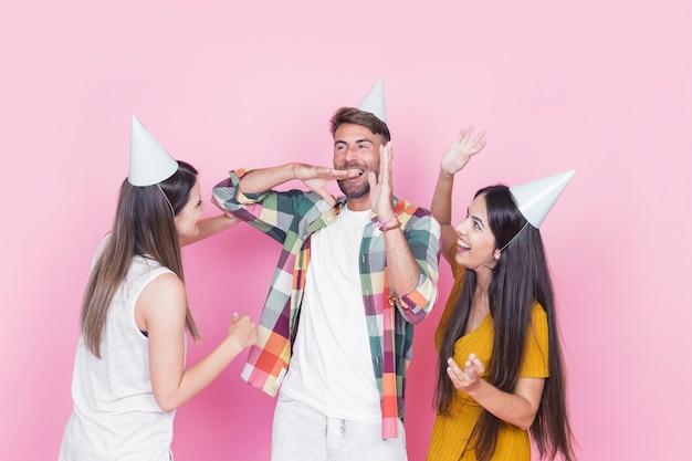 Groep gelukkige vrienden die op roze achtergrond vieren