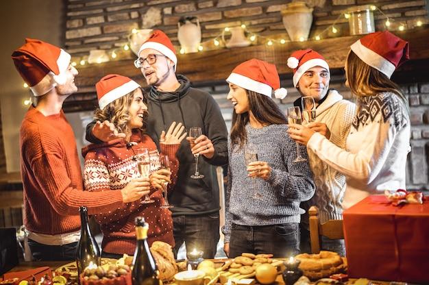 Groep gelukkige vrienden die op santahoeden kerstmis met wijn en zoet voedsel vieren bij dinerpartij