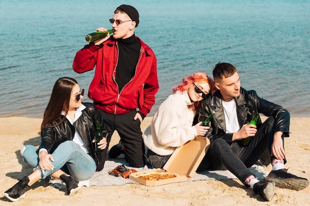 Groep gelukkige vrienden die partij op strand hebben
