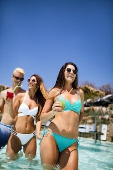 Groep gelukkige vrienden die plezier hebben met dansen bij het zwembad met cocktails
