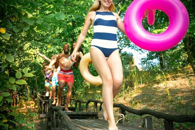 Groep gelukkige vrienden die plezier hebben tijdens het hardlopen om te zwemmen op de rivier