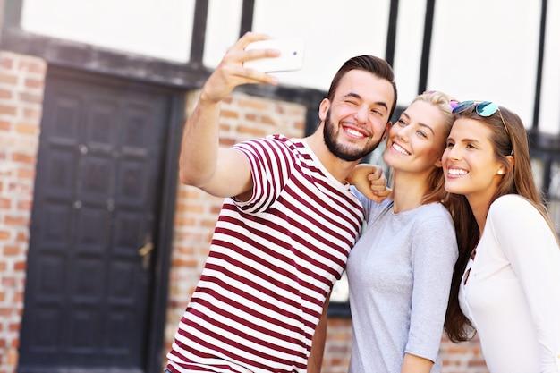 Groep gelukkige vrienden die selfie maken in de stad