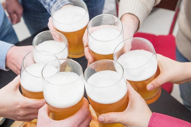 Groep gelukkige vrienden die thuis bier drinken en roosteren