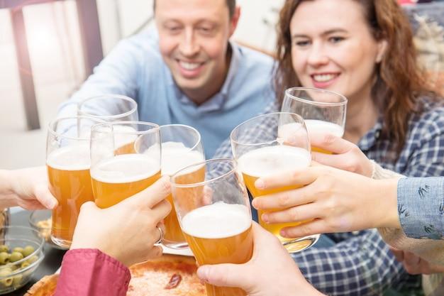 Groep gelukkige vrienden die thuis met bier juichen en samen plezier hebben bij het eten van italiaanse pizza
