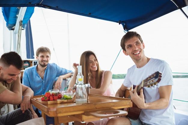 Groep gelukkige vrienden die wodkacocktails drinken en gitaar in een boot spelen