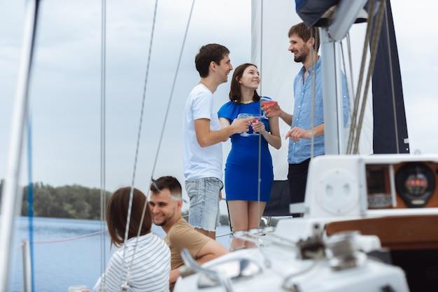 Groep gelukkige vrienden die wodkacocktails drinken op bootfeest buiten, zomer, Gratis Foto