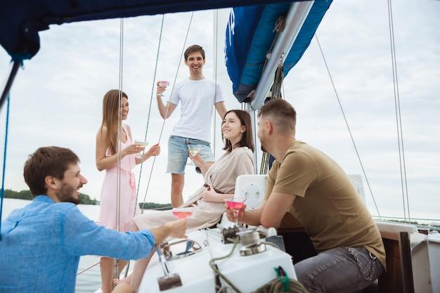 Groep gelukkige vrienden die wodkacocktails in een boot drinken