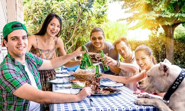 Groep gelukkige vrienden eten en roosteren bij tuin barbecue