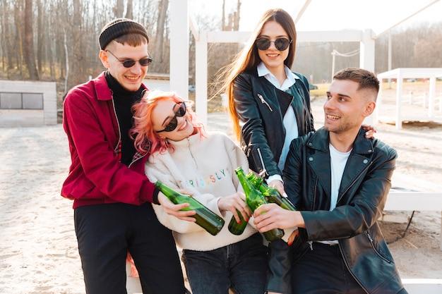 Groep gelukkige vrienden met bier dat samen lacht