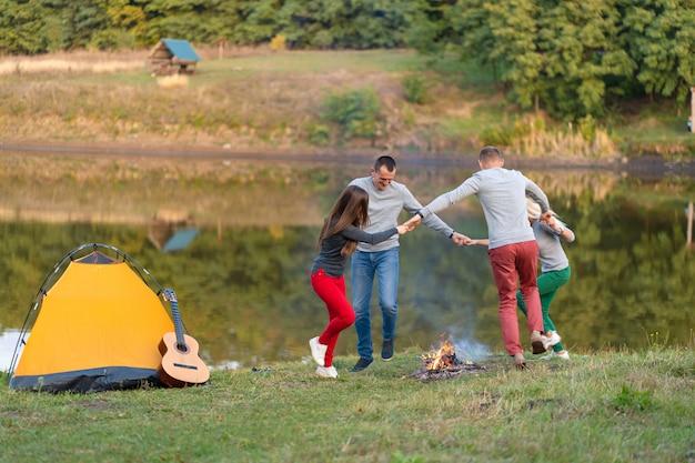 Groep gelukkige vrienden met gitaar, plezier buiten, dansen en springen in de buurt van het meer in het park de mooie hemel. campingplezier