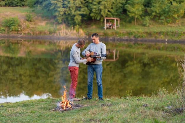 Groep gelukkige vrienden met gitaar, plezier buiten, dansen en springen in de buurt van het meer in het park