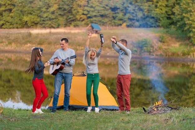 Groep gelukkige vrienden met gitaar, plezier buiten, dansen en springen in de buurt van het meer