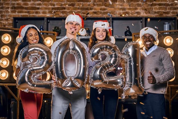 Groep gelukkige vrienden nieuwjaar vieren samen met ballonnen.