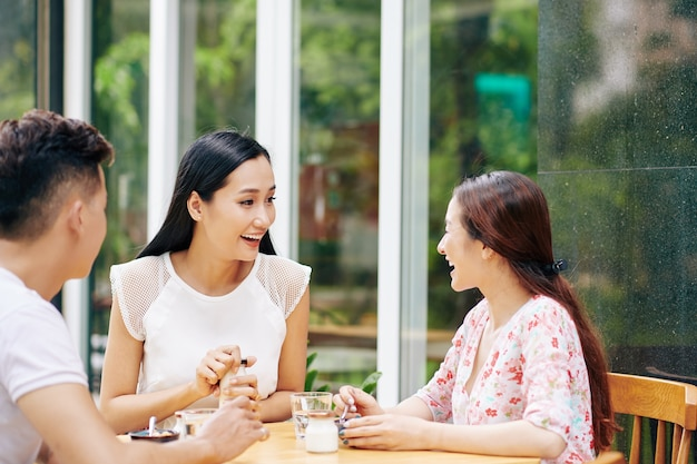 Groep gelukkige vrienden ontbijten op terras