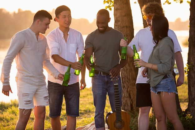 Groep gelukkige vrienden rammelende bierflesjes tijdens picknick op het strand in de zon. lifestyle, vriendschap, plezier, weekend en rustconcept. ziet er vrolijk, gelukkig, vierend, feestelijk uit.