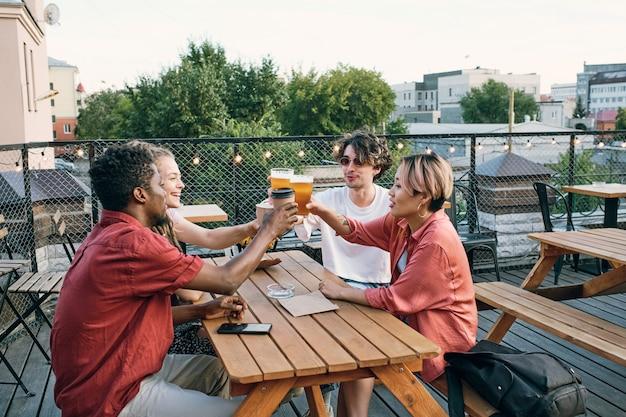 Groep gelukkige vrienden roosteren aan tafel in het buitencafé