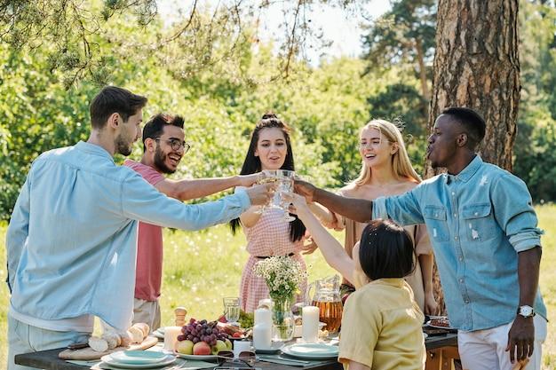Groep gelukkige vrienden van verschillende etnische groepen roosteren boven tafel geserveerd voor het diner terwijl ze onder de boom in natuurlijke omgeving staan