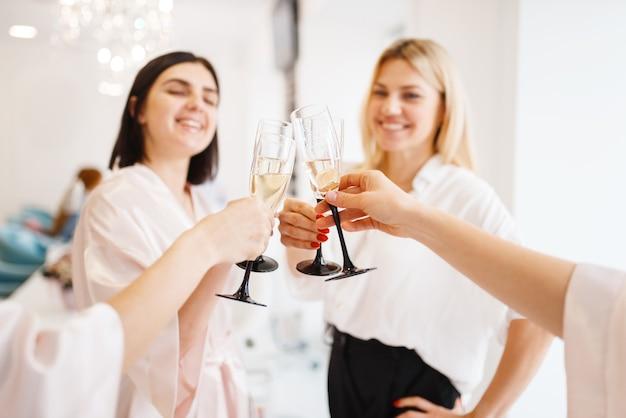 Groep gelukkige vriendinnen gerinkelglazen in de schoonheidssalon.