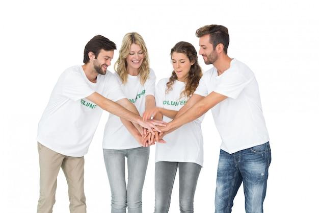 Groep gelukkige vrijwilligers met handen samen