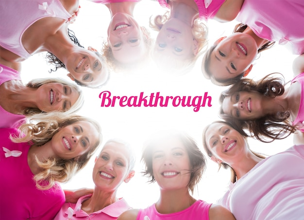 Groep gelukkige vrouwen in cirkel die roze voor borstkanker dragen