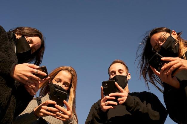 Groep gemaskerde vrienden die smartphones gebruiken