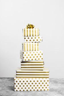 Groep geschenken in wit en goud papier op een grijze ondergrond