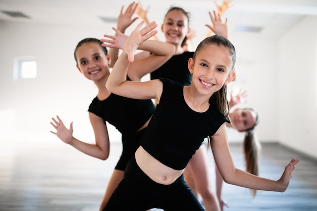 Groep geschikte gelukkige kinderen die samen ballet in studio uitoefenen