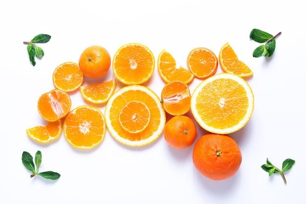 Groep gesneden sinaasappelen en mandarijnen met muntblaadjes op wit