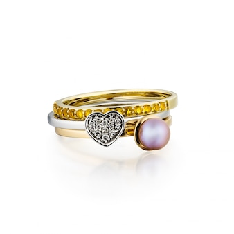 Groep gestapelde diamantringen geïsoleerd op witte achtergrond, witgoud, geel goud, inbegrepen het knippen weg. extreem dichtbij.