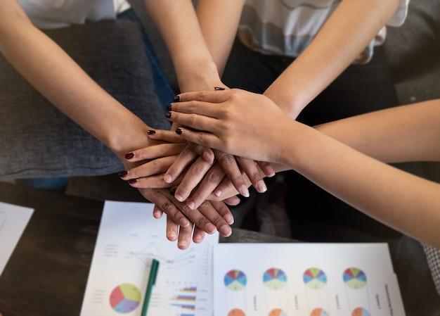 Groep gestapelde jonge mensenhanden