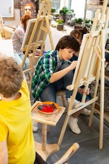 Groep getalenteerde leerlingen kleuren hun prent in de kunstacademie