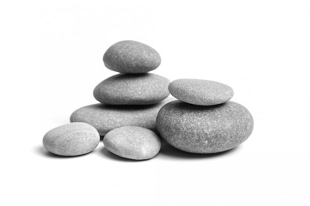 Groep gladde grijze stenen. zee kiezel. gestapelde kiezelstenen die op witte achtergrond worden geïsoleerd
