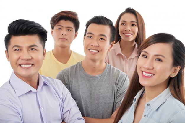 Groep glimlachende aziatische mannen en vrouwen die zich verenigen kijken
