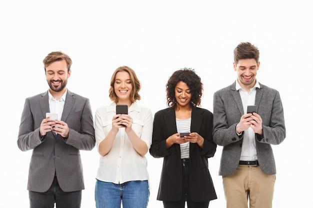 Groep glimlachende jonge bedrijfsmensen die mobiele telefoons met behulp van