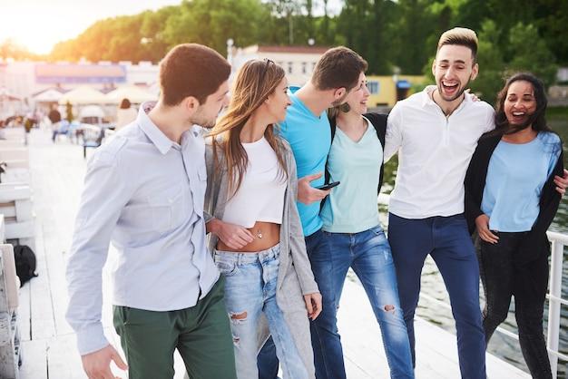 Groep glimlachende jonge en succesvolle mensen op vakantie op het dok.