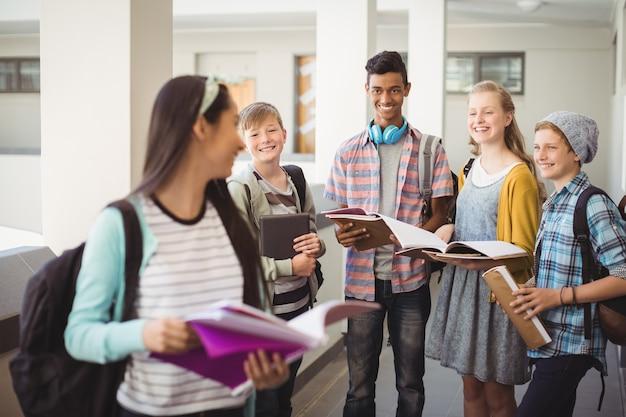 Groep glimlachende studenten die zich met notitieboekje in gang bevinden