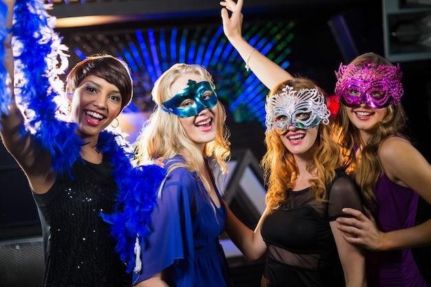Groep glimlachende vrienden die op dansvloer dansen