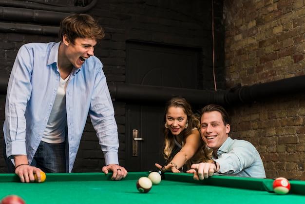 Groep glimlachende vrienden die snooker spelen die in club genieten van