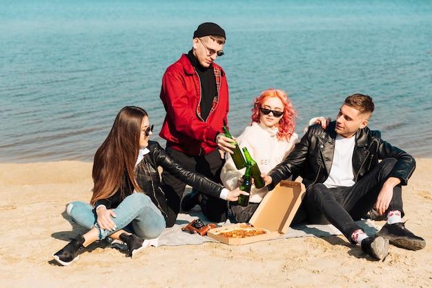 Groep glimlachende vrienden op picknick bij strand