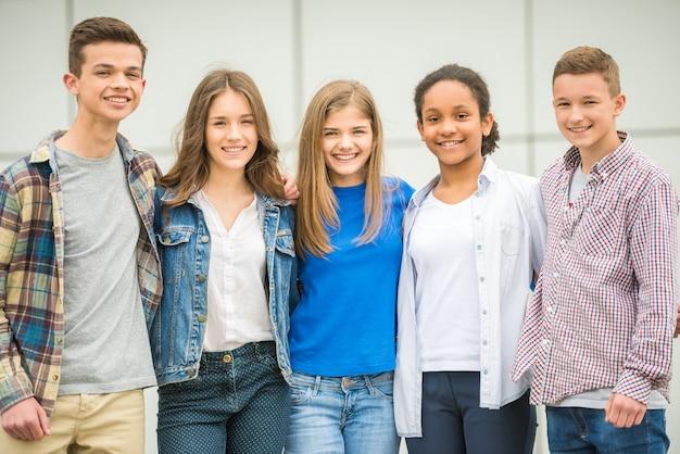 Groep glimlachende vrolijke tieners die pret na lessen hebben