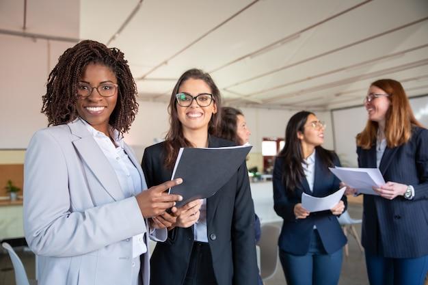 Groep glimlachende vrouwen die document documenten houden