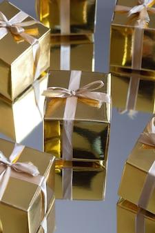 Groep gouden fonkelende geschenkdozen op grijze achtergrond met reflectie