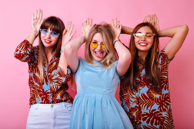 Groep grappige hipster meisjes die konijnenoren imiteren door hun handen, tong tonen en glimlachen, grappige jeugdfeeststijl, trendy zomerkleding en kleurrijke glazen