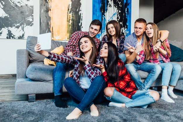 Groep grappige jonge vrienden die thuis op de bank zitten en samen selfie maken..