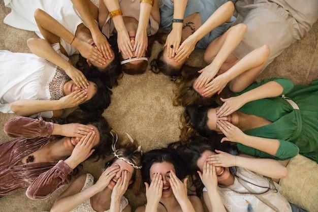 Groep grappige mode vriendinnen poseren bedekkend ogen door handen liggend cirkel genieten van vriendschap