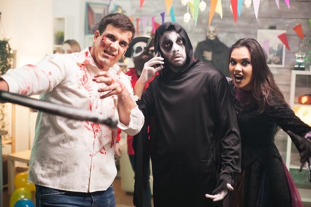 Groep griezelig monster bij halloween-viering. zombie met bijl.