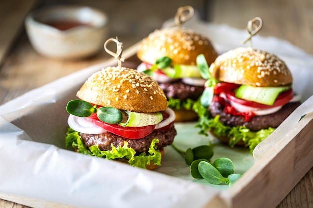 Groep hamburgers met tomatensaus op een houten dienblad.