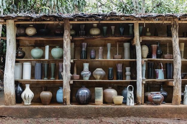Groep handgemaakte keramische keukenartikelen gerangschikt op planken
