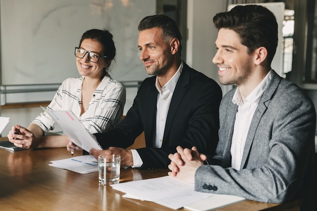 Groep hapy zakenmensen in formele pakken zittend aan tafel in kantoor, en de behandeling van hervatten van nieuw personeel tijdens sollicitatiegesprek - business, carrière en plaatsing concept